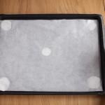 Tarte au citron meringuée revisitée - Coller la feuille de papier sulfurisé sur la plaque avec une pointe de meringue aux 4 coins.